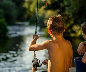 Niño practicando pesca deportiva con caña